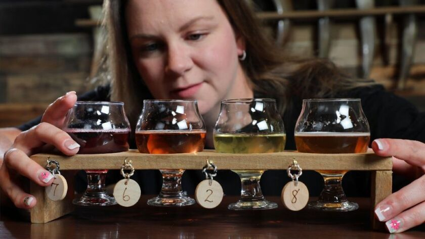 Katie Fallon, a barmaid at Twisted Horn Mead & Cider in Vista, inspects a flight of four samples of the company's products last week.