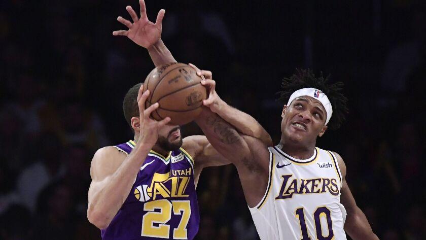 Lakers forward Jemerrio Jones battles Jazz center Rudy Gobert for a rebound Sunday.