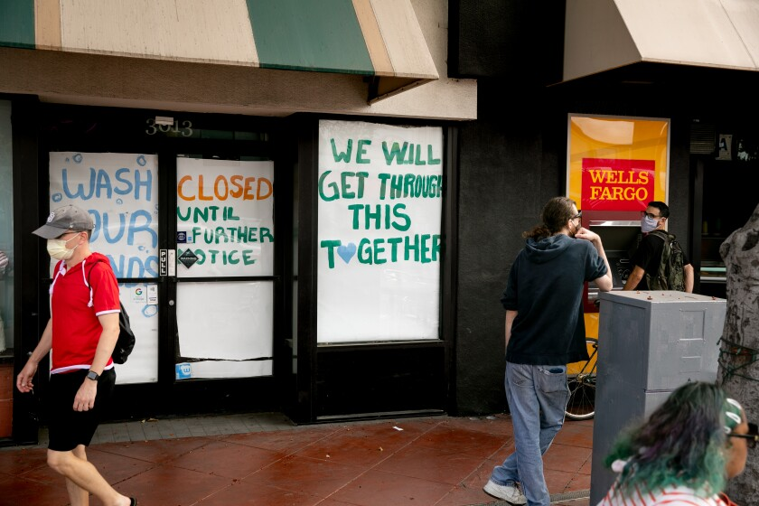 "People walk by a business papered with signs reading ""Closed Until Further Notice"" and ""Wash Your Hands."""