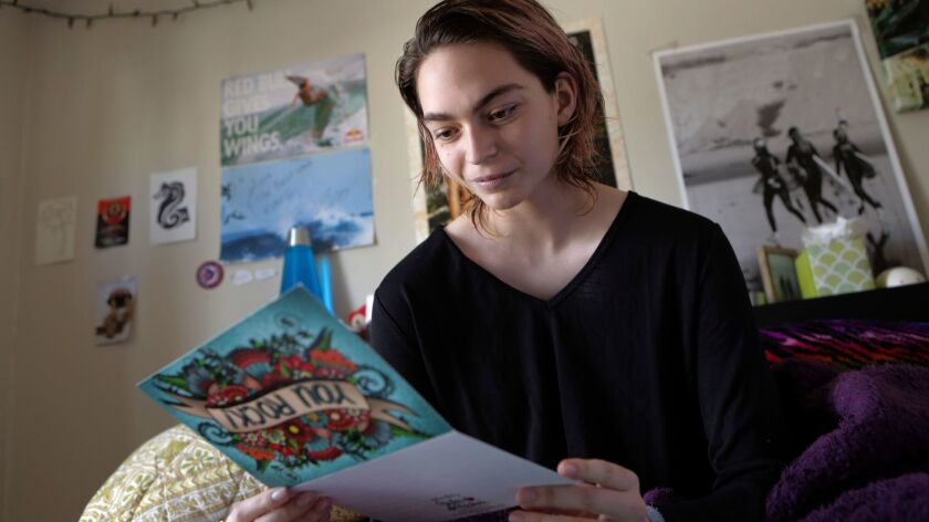 Kira Stanley, 15, in her room at her Encinitas home Friday reading some of the cards and letters she