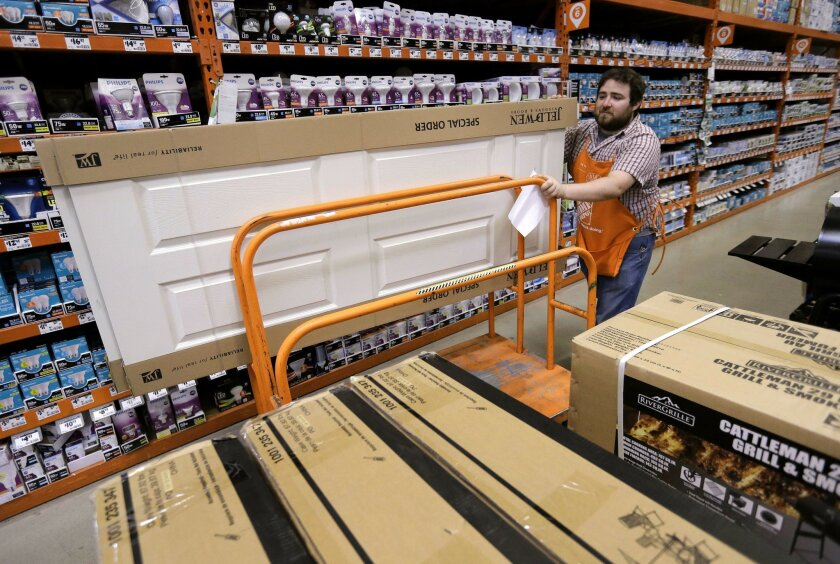 In this Wednesday, May 18, 2016, photo, Home Depot door and window specialist Joe Choiniere, of Woonsocket, R.I., moves a door down an isle at a Home Depot store location, in Bellingham, Mass. On Friday, July 15, 2016, the Commerce Department reports on business stockpiles in May. (AP Photo/Steven Senne)