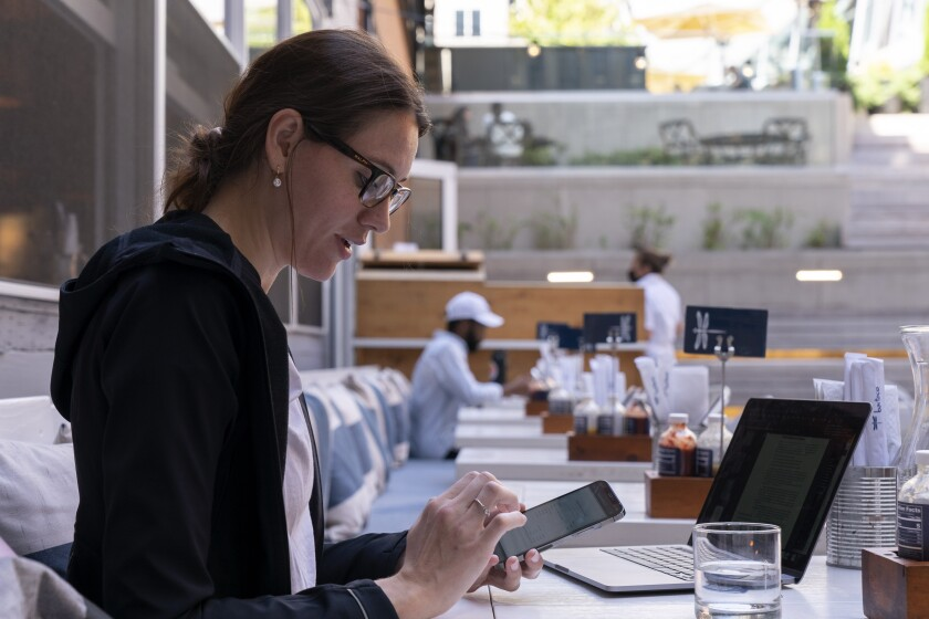 """Baylee Bowers pays for her lunch using her cell phone at Bartaco in Arlington, Va., on Thursday, Sept. 2, 2021. The restaurant is using an automated app for ordering and payments. Instead of servers they use """"food runners"""" to get orders to tables. """"I like it,"""" says Bowers of the automation, """"it was easy. I'm a flight attendant so as long as automation doesn't come for my job I'm ok with it."""" (AP Photo/Jacquelyn Martin)"""