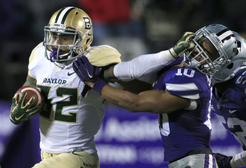 Baylor running back Shock Linwood (32) stiff-arms Kansas State defensive back Donnie Starks (10) during the second half of an NCAA college football game in Manhattan, Kan., Thursday, Nov. 5, 2015. Baylor defeated Kansas State 31-24. (AP Photo/Orlin Wagner)