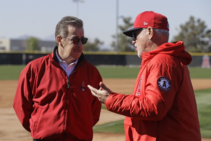 Angels manager Joe Maddon, right, speaks with Angels owner Arte Moreno during spring training in Tempe, Ariz., on Feb. 13.