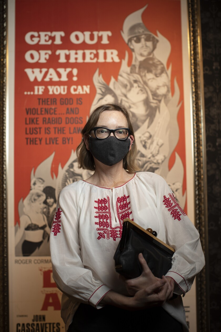 A woman wearing a dark mask and holding a dark purse stands in front of a movie poster.