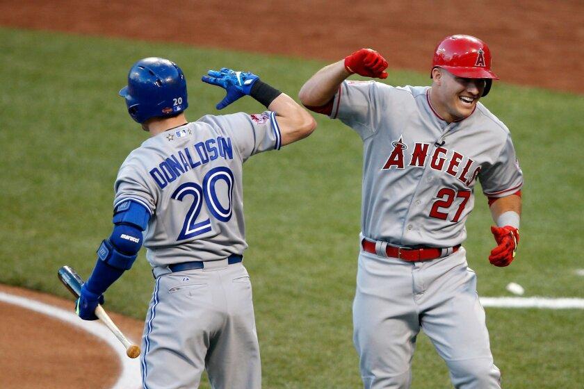 Mike Trout (d) de los Angels celebra con Josh Donaldson, de Toronto Blue Jays, por la victoria del equipo de la Liga American en el Great American Ball Park de Cincinnati, Ohio.