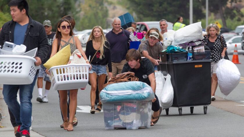 It was move in day at San Diego State on Friday, with students from all over the country making the SDSU dorms home. Kirk Proving pushes a crate full of his girlfriend Eunby Jun, left, carrying clot