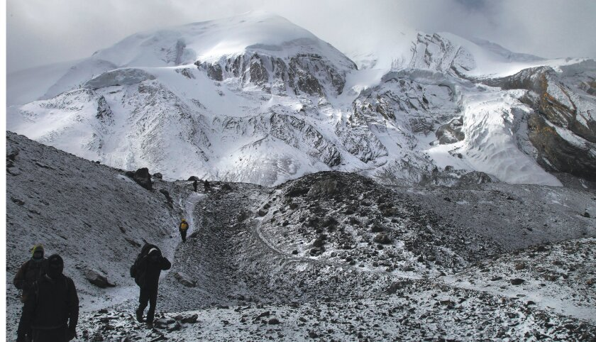 Hikers approach after trekking from the opposite side of the nearby Thorong-La Pass.