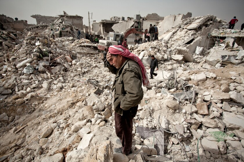 A man stands amid the rubble of his house in Aleppo, Syria.