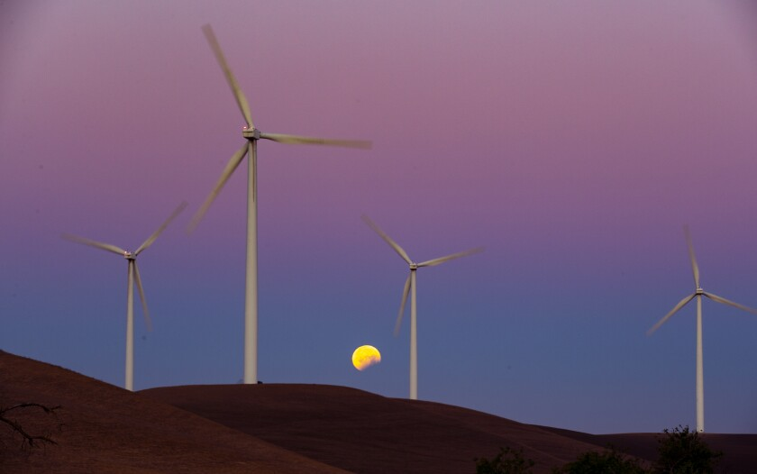 Wind turbines spin with the moon in the background