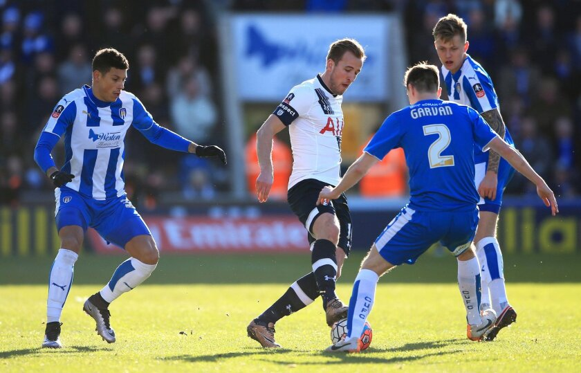 Tottenham Hotspur's Harry Kane, center, battles for the ball with Colchester United's Owen Garvan, second right, during the English FA Cup, fourth round soccer match at the Weston Homes Community Stadium, Colchester, England, Saturday Jan. 30, 2016. (Nick Potts/PA via AP) UNITED KINGDOM OUT