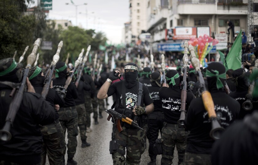 Masked members of the Hamas Palestinian militant group attend a rally to commemorate the 27th anniversary of the group in Gaza City.