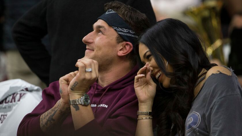 Johnny Manziel sits with his fiance Bre Tiesi during a college basketball game between Kentucky and Texas A&M on Feb. 10.