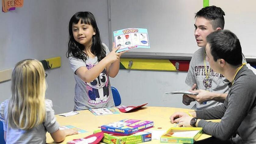Concordia University students play a bingo game with resident children of the Orange County Rescue Mission in February. The Rescue Mission is seeking donations of school supplies for its Village of Hope in Tustin.
