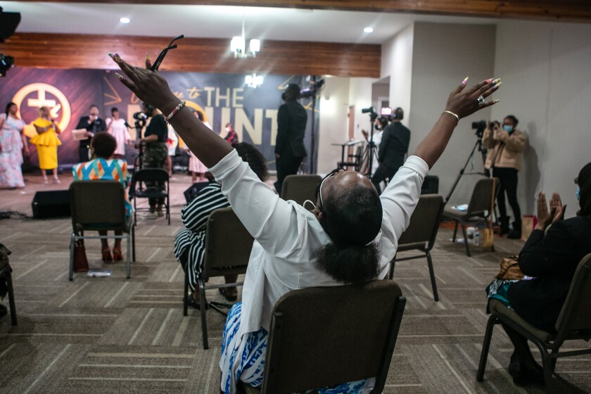 LOS ANGELES, CA - APRIL 04: A church member with hands raised worships during Easter Sunday service at New Mount Calvary Missionary Baptist Church amidst the pandemic on Sunday, April 4, 2021 in Los Angeles, CA. (Jason Armond / Los Angeles Times)