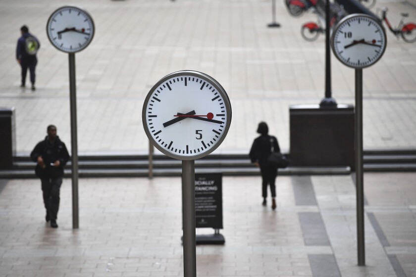 """People walk across the plaza, around the old normal morning time 'rush hour', at Canary Wharf in central London, Thursday Sept. 3, 2020. Workers are being encouraged to return to their offices, with a Government information campaign reminding people about the efforts taken to make workplaces safe and """"Covid-secure"""". (Victoria Jones/PA via AP)"""