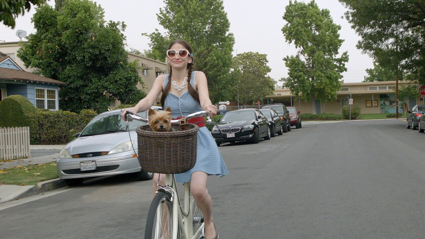 "Shaina Vorspan as Jill on a bike with Leila in ""Gone Doggy Gone."""