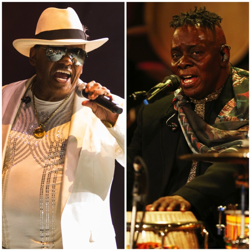 A white-hatted Ronald Isley and a drumming Philip Bailey sing into microphones.