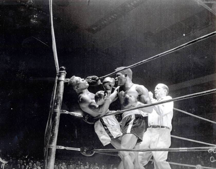 """Emile Griffith, center, delivers a crushing blow to Benny """"Kid"""" Paret in their famed 1962 bout in Madison Square Garden. Paret died 10 days later."""