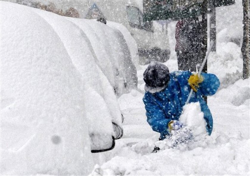 A woman shovels snow in downtown Podgorica, Montenegro, Saturday, Feb. 11, 2012. Montenegro is struggling to maintain its power grid amid record low temperatures in the Balkan country and much of Europe. (AP Photo/Risto Bozovic)