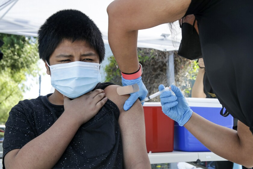 A 12-year-old, with a sleeve rolled up, is injected with a COVID-19 vaccine.