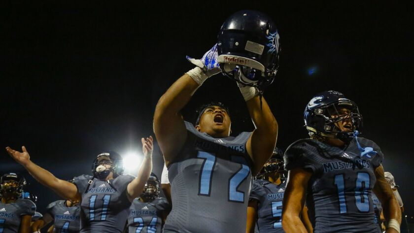 Otay Ranch's Chad Sapinoso (72) and Dylan Zolezzi (10) rile up the crowd after the Mustangs' comeback victory over Point Loma.