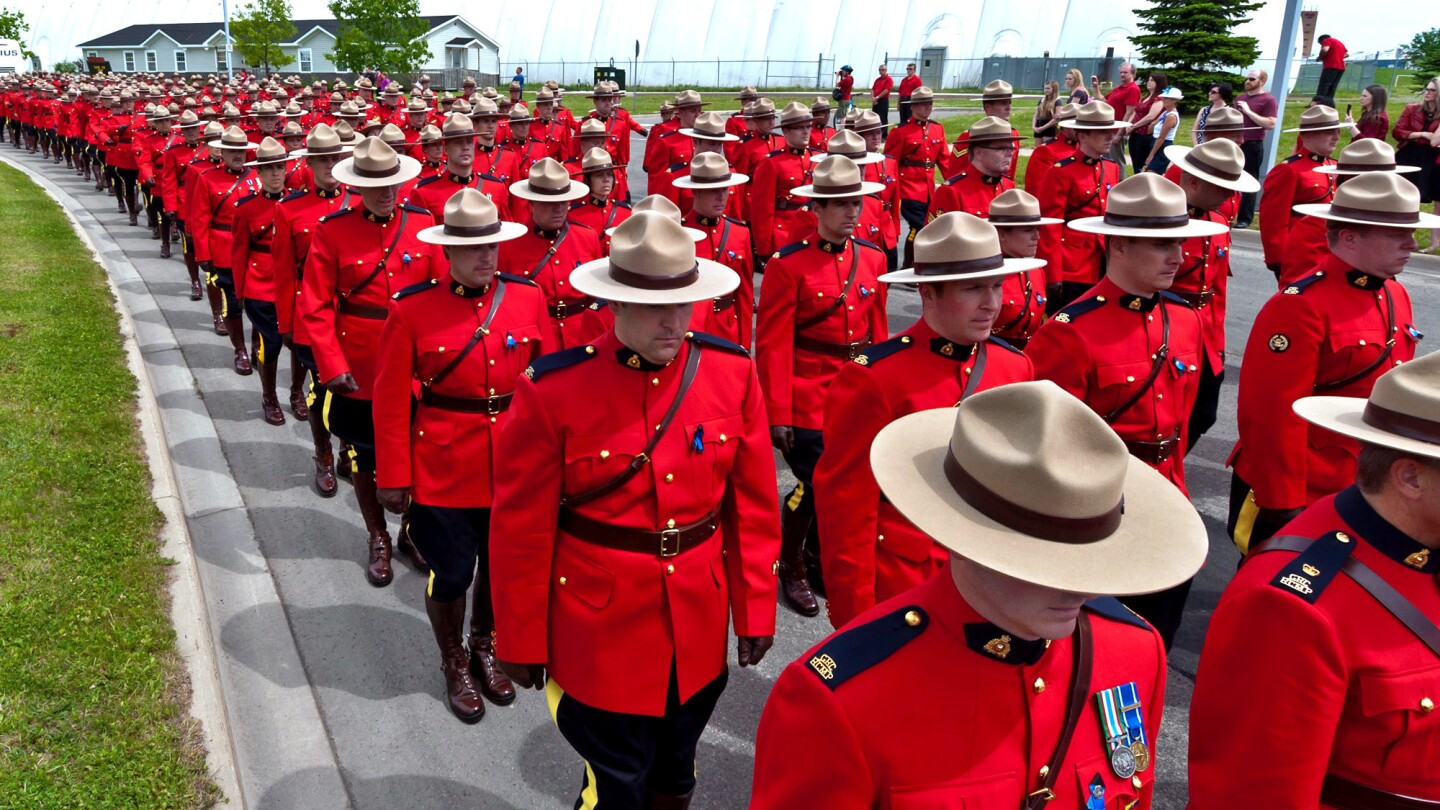 Royal Canadian Mounted Police officers march during a funeral procession for three officers Tuesday in Moncton, New Brunswick. The officers were gunned down June 4 after responding to a report of an armed man in a Moncton residential neighborhood.