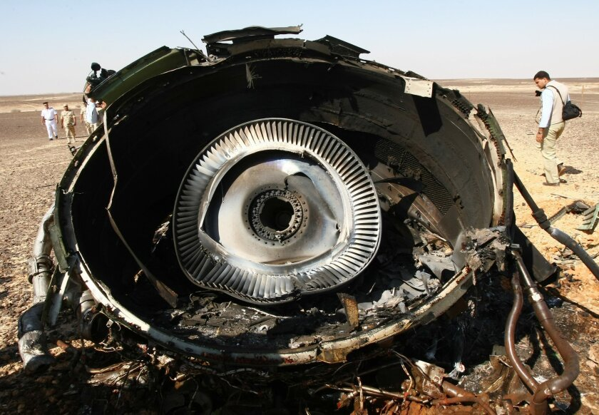 In this photo made available Monday, Nov. 2, 2015, and provided by Russian Emergency Situations Ministry, Egyptian Military experts examine a piece of an engine at  the wreckage of a passenger jet bound for St. Petersburg in Russia that crashed in Hassana, Egypt, on Sunday, Nov. 1, 2015. The Russia