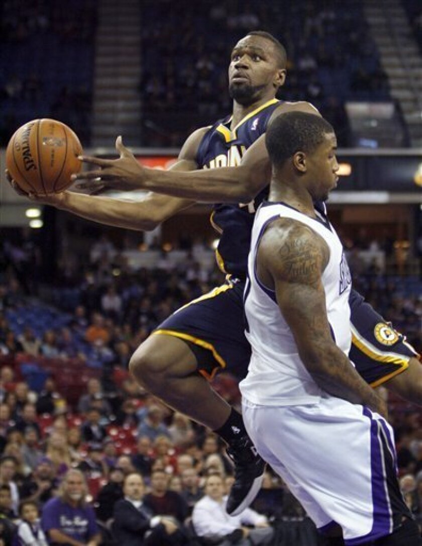 Indiana Pacers guard Sam Young, left, drives to the basket past Sacramento Kings defender Thomas Robinson during the first half of an NBA basketball game in Sacramento, Calif., on Friday, Nov. 30, 2012. (AP Photo/Steve Yeater)