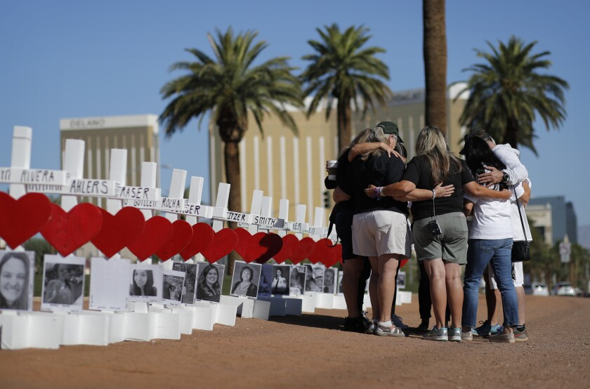 People pray at a makeshift memorial for shooting victims, Tuesday, Oct. 1, 2019, in Las Vegas, on the anniversary of the mass shooting two years earlier. (AP Photo/John Locher)