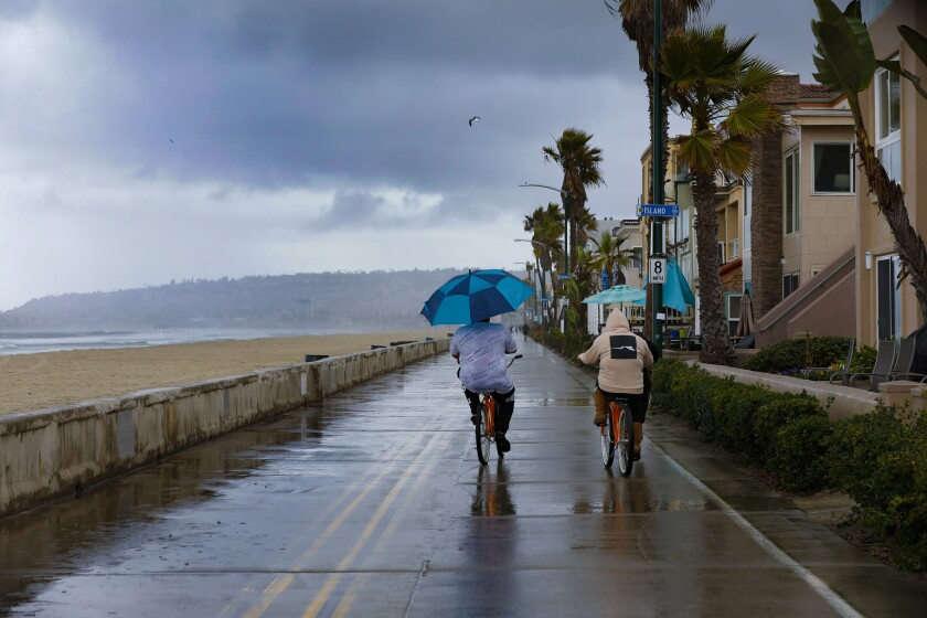 At a nearly empty boardwalk in Mission Beach on Saturday, the rain didn't stop a few who chose to enjoy a wet bike ride.