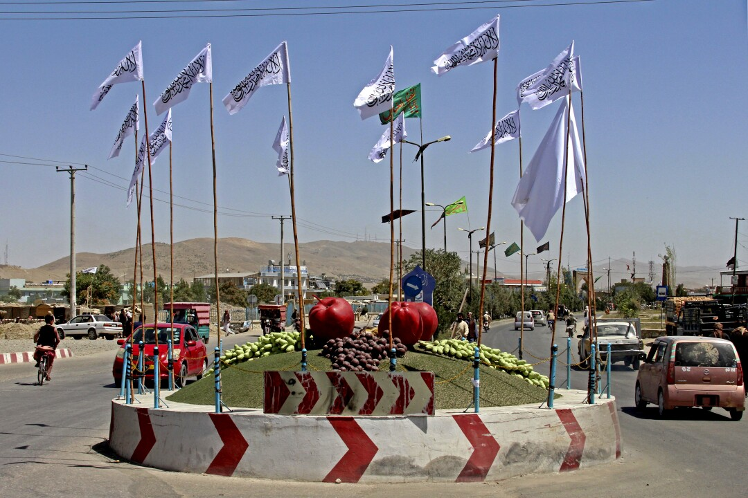 White Taliban flags surround a traffic circle that is decorated with sculptures of fruit