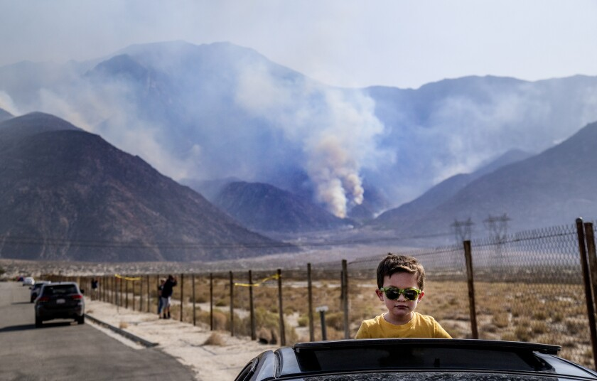 Elias Lomeli of Desert Hot Springs watches firefighting helicopters refill with water from his car's sunroof.