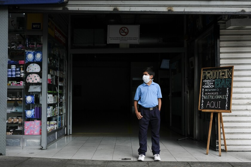 A boy, wearing a protective mask as a precaution against the spread of the new coronavirus, stands outside a store waiting his mother to finish shopping, in Caracas, Venezuela, Friday, March 13, 2020. Venezuela's Vice President Delcy Rodriguez confirmed Friday the first two cases of the new coronavirus in the South American country. The vast majority of people recover from the new virus. (AP Photo/Matias Delacroix)