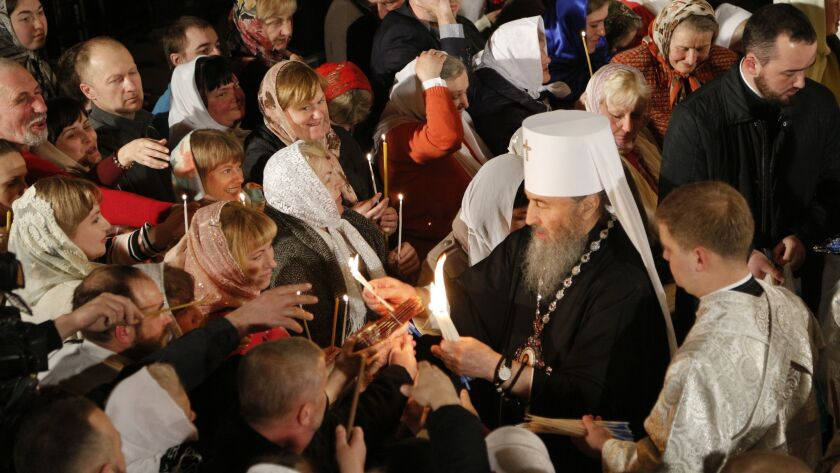 The head of the Ukrainian Orthodox Church under the Moscow Patriarchate, Metropolitan Onufri, lights believers' candles during the Easter service April 7 in the Monastery of Caves in Kiev, Ukraine.