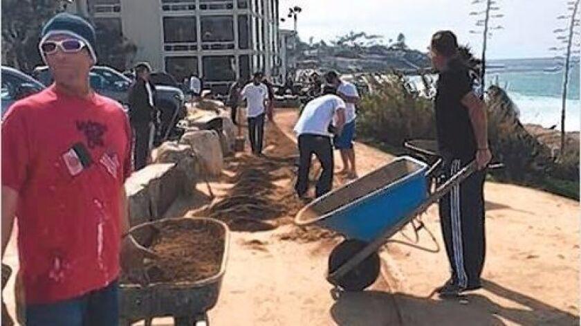 Volunteers lay decomposed granite (DG) on the walkway along WindanSea Beach.