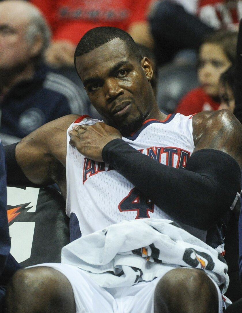 Atlanta Hawks forward Paul Millsap (4) holds his shoulder after being injured on the court during the first half of an NBA basketball game against the Brooklyn Nets, Saturday, April 4, 2015, in Atlanta. (AP Photo/John Amis)