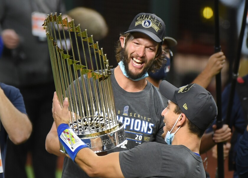 Clayton Kershaw, left, and Austin Barnes hold the trophy after the Dodgers' 2020 World Series win.