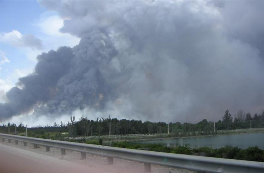 Un avión sobrevuela la zona cubierta por el humo provocado por un nuevo incendio forestal a orillas de los Everglades (pantanos). EFE/Archivo
