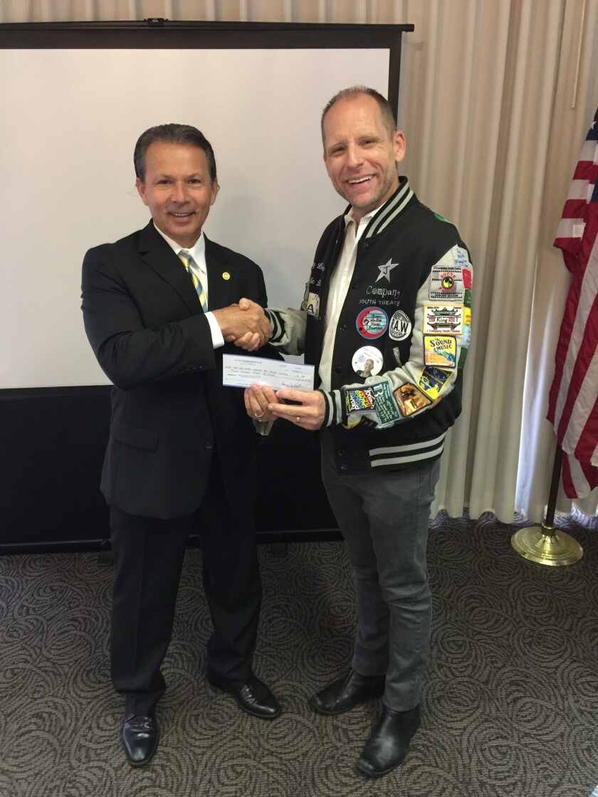 Mark Powell (left) of La Jolla Sunrise Rotary gives a check to Joey Landwehr of J*Company youth theater to fund a performance for foster teens.