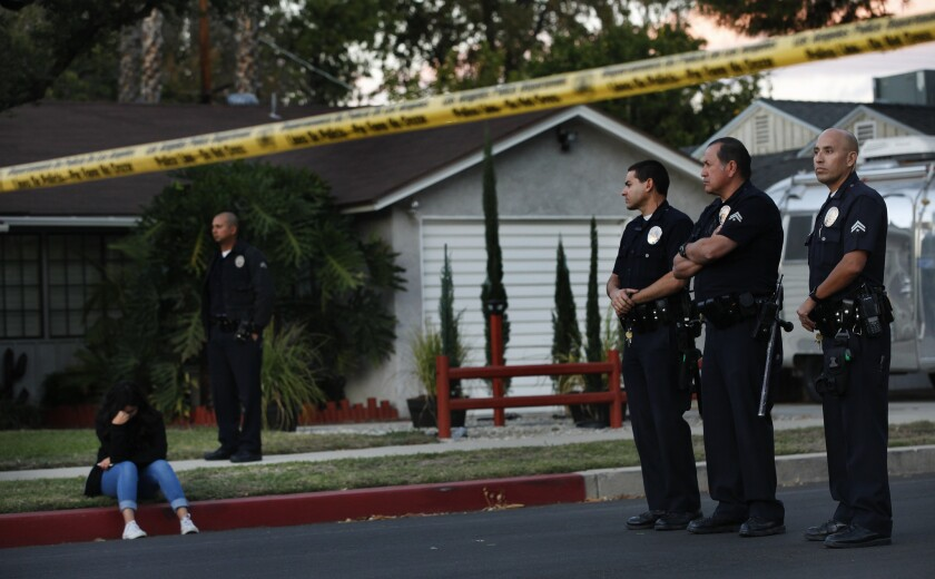 Los Angeles police officers stand near the scene of a shooting last fall in Lake Balboa, where police fatally shot a 34-year-old man.