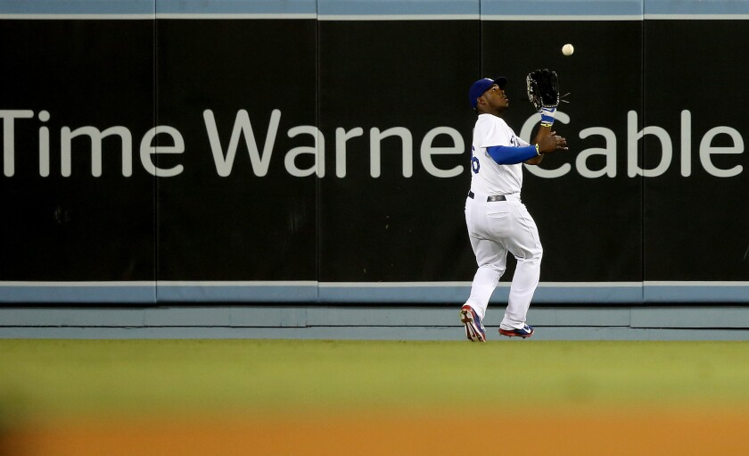 Dodger center fielder Yasiel Puig makes a catch in front of a Time Warner Cable advertisement on the outfield wall during a game against the Angels in 2014 at Dodger Stadium in Los Angeles.