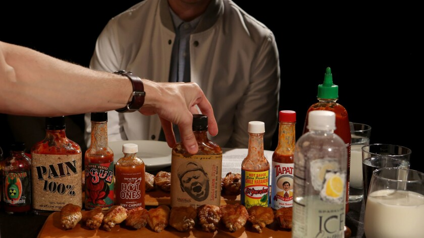 """A collection of sauces used to coat the hot wings on the show """"Hot Ones"""""""