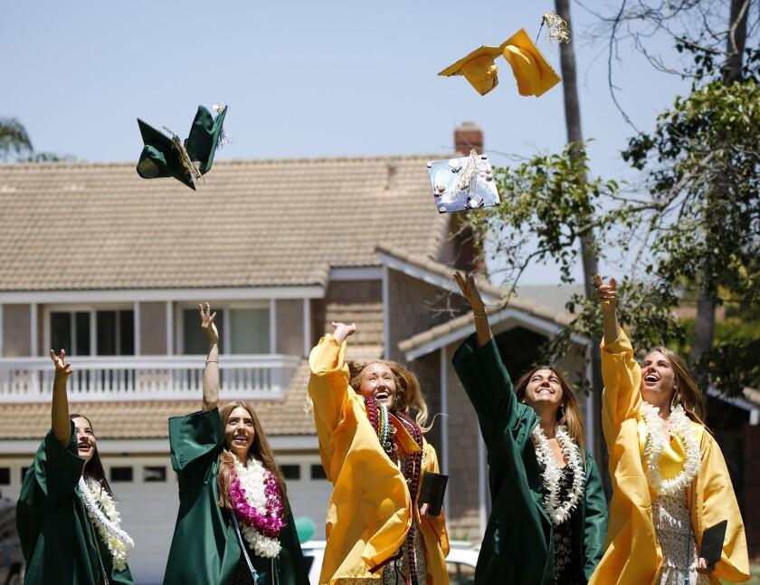 A group of Edison High School graduates toss their caps into the air in Huntington Beach.