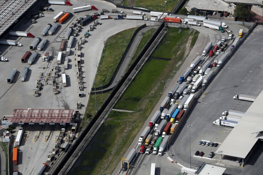 Commercial freight trucks line up to cross into the United States from Mexico.