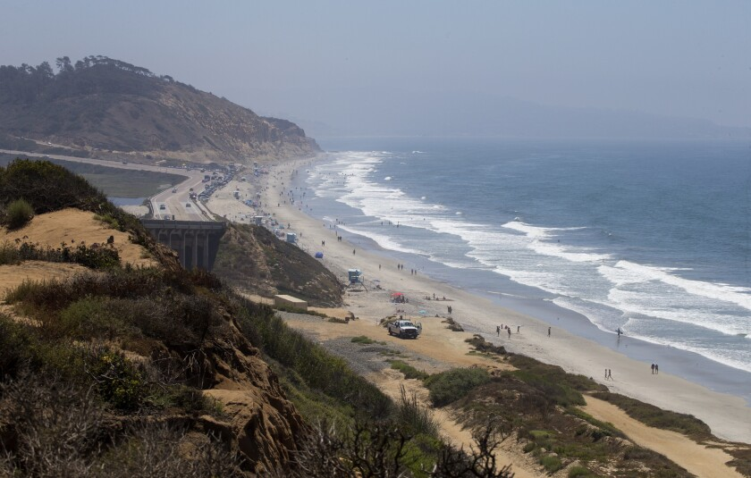 Visitors stroll along Torrey Pines State Beach in San Diego.