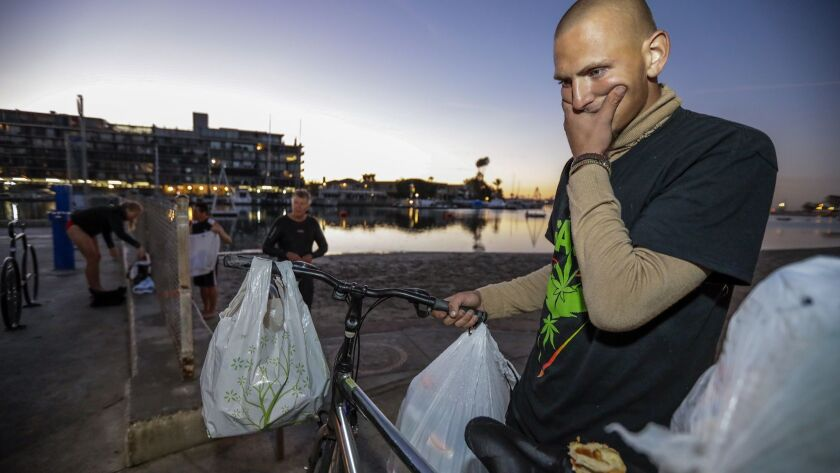 Chase Grant, 20, who has been living on the streets for seven months, collects recyclables in Belmont Shore, where residents blaming crime on the homeless population went on an early morning patrol march Friday.