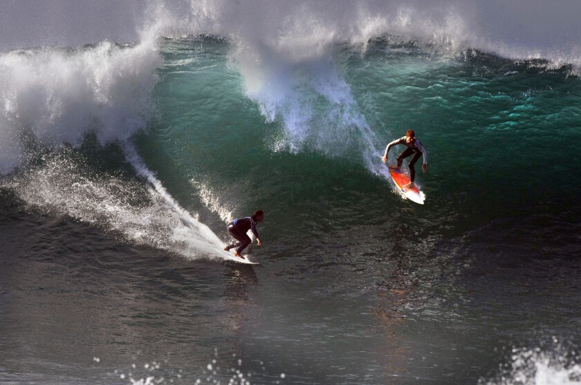 Surfers slide down a huge wave Wednesday at the Wedge in Newport Beach.