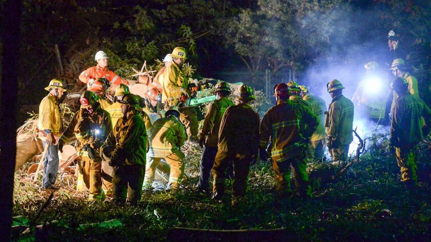 Los Angeles County firefighters work on a large eucalyptus tree that fell on a wedding party Saturday in Whittier.
