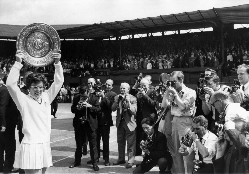 Billie Jean King hoists the Venus Rosewater Dish, her first Wimbledon singles win in 1966, for a crowd of photographers.
